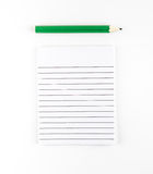 Top view of Ruled paper notepad with green pencil on white backg Royalty Free Stock Photos