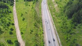 Top view of rural road. Clip. Rural highway with traffic in forest. Suburban highway with cars. Travel.  stock footage