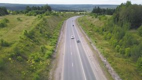 Top view of rural road. Clip. Rural highway with traffic in forest. Suburban highway with cars and trucks. Travel and. Transportation stock footage