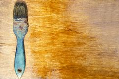 Top view of rustic paintbrush on the varnished wooden surface. Male hand holding old paintbrush and varnishing wooden surface with it stock photos