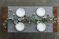 top view of rustic table setting with eucalyptus, tarnished cutlery, wine glasses, candles and empty plates on tabletop royalty free stock photo