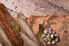 Top view of rye brown bread, dried up bay leaves, speckled quail eggs, grocery paper and seasonings on a wooden. Top view of brown rye bread, speckled fresh Royalty Free Stock Photography