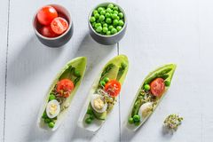 Top view of salad with avocado, asparagus in chicory. On white table Royalty Free Stock Photo