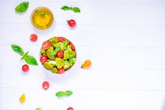 Top view Salad Bowl with cherry tomatoes, boiled broccoli, basil and fresh ingredients on the white wooden background. Healthy lif Stock Photos