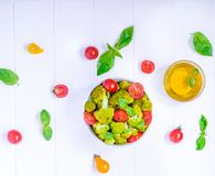 Top view Salad Bowl with cherry tomatoes, boiled broccoli, basil and fresh ingredients on the white wooden background. Healthy lif Stock Photo