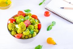 Top view Salad Bowl with cherry tomatoes, and broccoli and diet notebook on the white wooden background. Healthy lifestyle concept. Detox, diet, vegitarian Stock Images