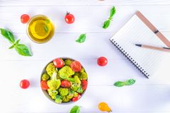 Top view Salad Bowl with cherry tomatoes, and broccoli and diet notebook on the white wooden background. Healthy lifestyle concept Royalty Free Stock Image