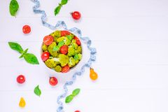 Top view Salad Bowl with cherry tomatoes, broccoli, fresh ingredients, measuring tape on the white wooden background. Healthy life Royalty Free Stock Images