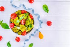 Top view Salad Bowl with cherry tomatoes, broccoli, fresh ingredients, measuring tape on the white wooden background. Healthy life Royalty Free Stock Photos