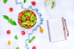 Top view Salad Bowl with cherry tomatoes, broccoli, measuring tape and diet book on the white wooden background. Healthy lifestyle. Concept. Detox, diet Stock Image