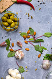 A top view of salad ingredients. Green stuffed olives in a glass bowl next to almond nuts and salad leaves on a gray royalty free stock photography