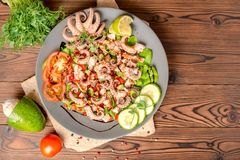 Top view of salad with tentacles of octopus, lime, avocado and l royalty free stock photography