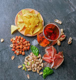 Top view of salty snacks and dark beer on a black background. Peanuts, pistachios, ham and basil with a glass of beer. A view from above on different tasteful Stock Image
