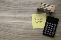 Top view of sand clock, calculator and yellow paper note written with Year End Review on wooden background with copy space
