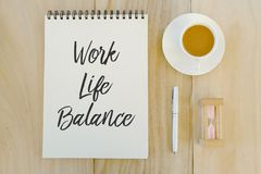 Top view of sand clock,a chup of coffee,pen and notebook written with Work Life Balance on wooden background. Top view of sand clock,a chup of coffee,pen and stock photos