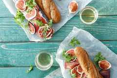 Top view sandwich ham mascarpone cheese figs wooden background. Top view sandwich with ham, mascarpone cheese and figs with glass of white wine on green wooden stock photos