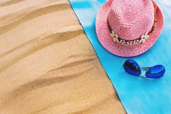 Top view of a sandy beach with a frame of blue towels with a hat and glasses. copy space and visible sand texture. Top view of a sandy beach with a frame of Royalty Free Stock Image