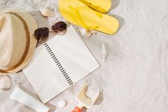 Top view of sandy beach with glasses and summer accessories. Background with copy space and visible sand texture. Border stock image