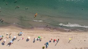Top view of sandy beach with tourists. People crowd relaxing on the beach. Aerial view of sandy beach with tourists. People crowd relaxing on the beach royalty free stock photography