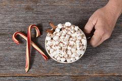 Top view of Santa Claus hand with a large mug of hot cocoa with marshmallows and cinnamon. stock image