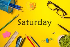 Top View of Saturday - word on yellow workplace with office or school supplies. Time Management and Schedule Concept.  royalty free stock image