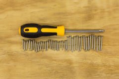Top view of screw driver and screw. On wood background Stock Photography