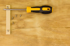 Top view of screw driver and screw. On wood background Royalty Free Stock Photos