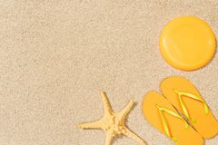 Top view of sea star, yellow flip flops and flying disk on sand stock photos