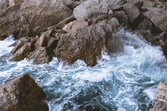 Top view of the sea waves that beat on the rocky coast. The sea wave beats on big stones stock photos