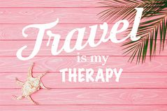 Pink wooden surface with lettering. Top view of seashell with palm leaves on pink wooden surface with travel is my therapy lettering stock illustration