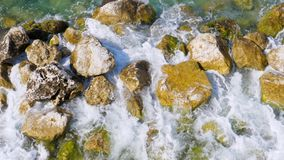 Large Waves Hit The Stone Shore Of The Turquoise Sea With Crystal Clear Water. Top view of the seashore with huge stones, which are struck by huge waves of azure stock footage