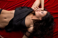 Top view of seductive brunette lying on red sheet Stock Images