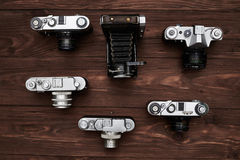 Top view of the selection of six old cameras over wooden grunge Stock Image