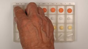 TOP VIEW: Senior male hand takes a pill from a plastic pill organizer Stock Image