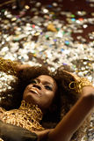 Top view of sensual attractive young woman with gold lips lying on background shining confetti Stock Photography