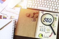 Top view of SEO and graph paper with magnifying glass, money coin. On working table Stock Image