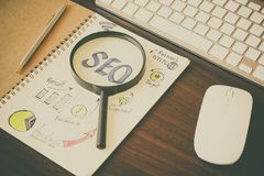 Top view of SEO and graph paper with magnifying glass, money coin. On working table Stock Photo