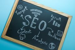 Top view of SEO Search Engine Optimization on black board on blu Royalty Free Stock Image