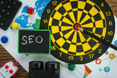 Top view of SEO search engine optimization website promotion c. Oncept with pencil, dart, web analytics graph and binoculars in flat lay stock image