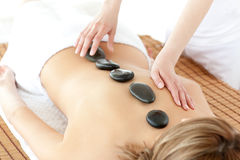 Top view of a serene woman having a stone therapy. Lying on a massage table Stock Images