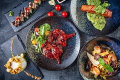 Top view on served food on dark background table. European cuisine fried chicken, sushi roll, seafood pasta, dessert and roasted stock images