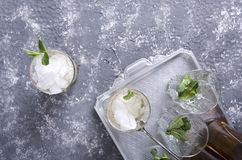 Top view of served mint julep drink on the vintage silver tray. Glasses and mint in it, crushed ice and bottles of alcohol beverag. Glasses of mint julep.Table stock image