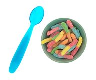 Sugar coated gummy worms in a bowl with a spoon. Top view of a serving of sugar coated sour tasting colorful gummy worms in a breakfast bowl with a blue plastic Royalty Free Stock Photography
