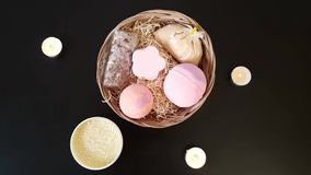 Top view of the set of cosmetics lying on the table. Basket with bath bombs, salt and soap. Burning candle. Romantic atmosphere.  stock video footage