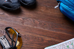 Top view of the set of equipment for travelling on brown wooden boards. Royalty Free Stock Photo
