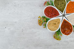 Top view on a set of tasty sauces with copy place and fresh herbs. Royalty Free Stock Photography