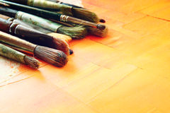 Top view of set of used paint brushes over wooden table Stock Image