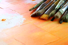 Top view of set of used paint brushes over wooden table Royalty Free Stock Images