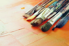 Top view of set of used paint brushes over wooden table Stock Photos