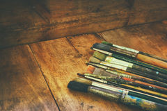 Top view of set of used paint brushes and palette over wooden table Royalty Free Stock Image